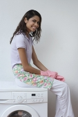 Woman with gloves sitting on washing machine and smiling at camera - Asia Images Group