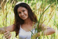 Young woman in high grass smiling at camera - Asia Images Group