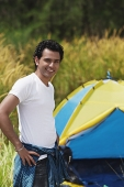 Young man camping smiling at camera - Asia Images Group