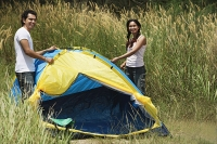 Young couple camping in high grass - Asia Images Group
