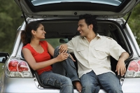 Young couple sitting in car boot - Asia Images Group