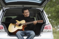 Young man sitting car boot playing guitar - Asia Images Group