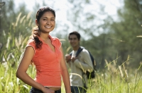 Young couple hiking in the wilderness and smiling at camera - Asia Images Group