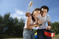 Young couple camping and cooking in the wilderness - Asia Images Group