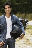 Young man with motorcycle helmet smiling at camera - Asia Images Group
