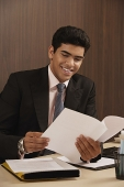 Businessman reading paper and smiling - Asia Images Group