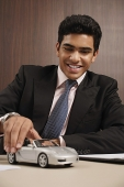 Businessman playing with toy car - Asia Images Group