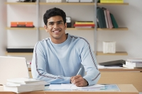 Young man sitting at desk and smiling at camera - Asia Images Group