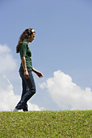Teen girl walking on grass - Nugene Chiang