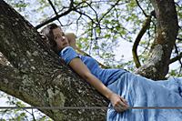 Teen girl lying in tree - Nugene Chiang