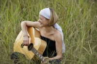 young woman playing guitar in field - Alex Mares-Manton