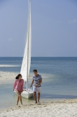 couple with sailboat on beach - Alex Mares-Manton