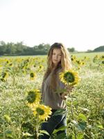 Young woman in field of sunflowers - Alex Hajdu