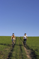 Young couple riding bicycles down hillside - Alex Mares-Manton