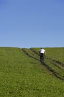 Young man riding bicycle up meadow path - Alex Mares-Manton