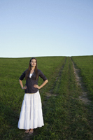 Young woman standing in grassy meadow - Alex Mares-Manton