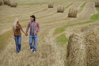 Young couple walking through field - Alex Mares-Manton