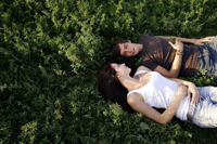 Young couple lying on back in field - Alex Mares-Manton