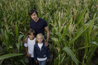 father with daughter and son standing in corn field - Alex Mares-Manton