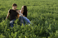 Young couple sitting in field - Alex Mares-Manton