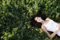 Young woman lying on her back in field - Alex Mares-Manton