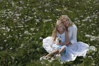 mother and daughter sitting in meadow of flowers - Alex Mares-Manton