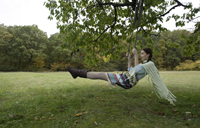 young woman swinging on tree swing - Alex Mares-Manton
