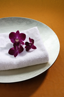 purple orchids on top of spa towel - Nugene Chiang