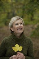 Senior woman holding autumn leaf - Alex Mares-Manton