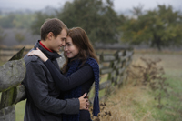 Young couple embracing against country fence - Alex Mares-Manton