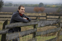 Young man leaning on country fence - Alex Mares-Manton