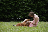 Young woman sitting on grass, holding her dog's face in hands - Alex Mares-Manton