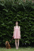 Young woman standing with dog on leash - Alex Mares-Manton