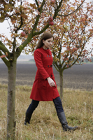 young woman walking through apple orchard - Alex Mares-Manton
