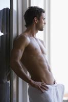 Profile of man standing by window, wearing towel - Alex Mares-Manton