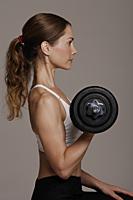 woman lifting free weights - Nugene Chiang