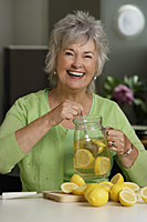 Mature woman making lemon aid. - Nugene Chiang