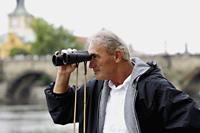 side view of mature man looking through binoculars - Alex Hajdu