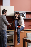 young couple in kitchen laughing and cooking together - Alex Mares-Manton
