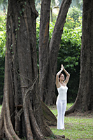 Young woman doing yoga under trees - Alex Mares-Manton